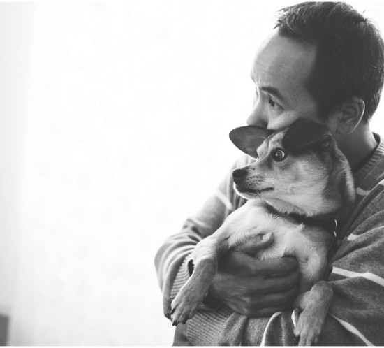 Los Angeles lifestyle photographer capturing a candid photograph of a man hugging a dog